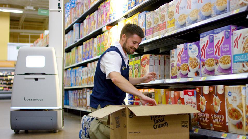 A Walmart associate restocks cereal as a Bossa Nova robot passes by.