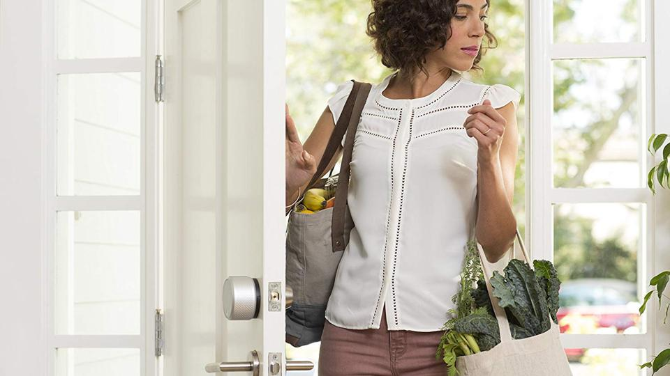 Person entering home with August Smart Lock Pro.