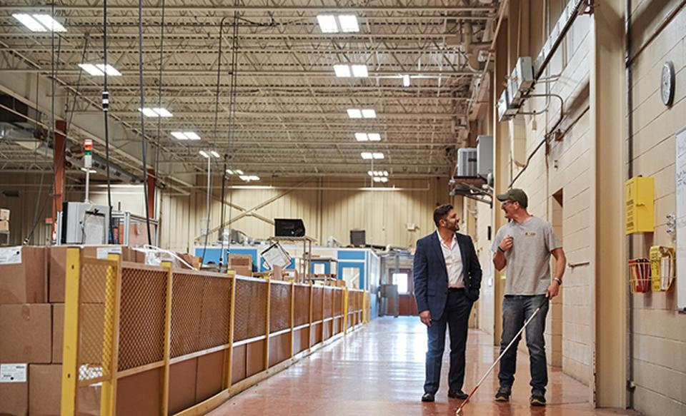 IBVI Chief Innovation Officer Emmanuel Vouvakis, left, chats with employee Justin Greenwood at the manufacturing facility.