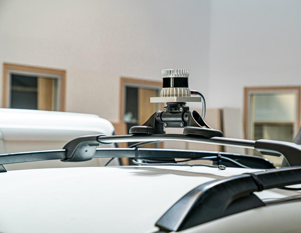 A mechanical spinning lidar mounter on the roof of a white car.