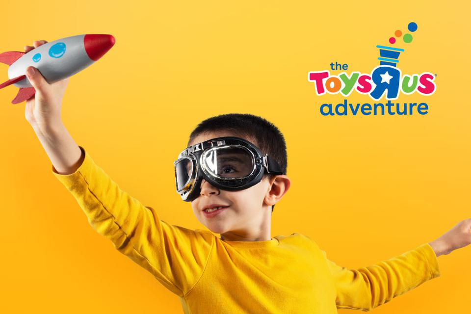The logo of the Toys R Us Adventure, with a photo of a child wearing googles and playing with a rocket ship