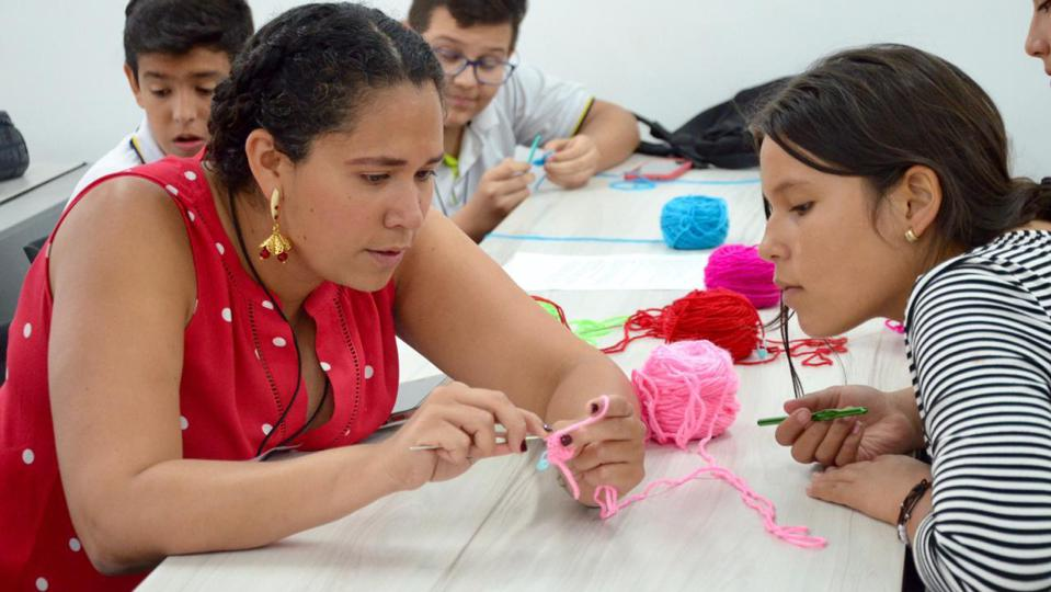 Biomedical Engineer Ana Maria Porras crochets with a student doing an event of Clubes de Ciencia in Bucaramanga, Colombia