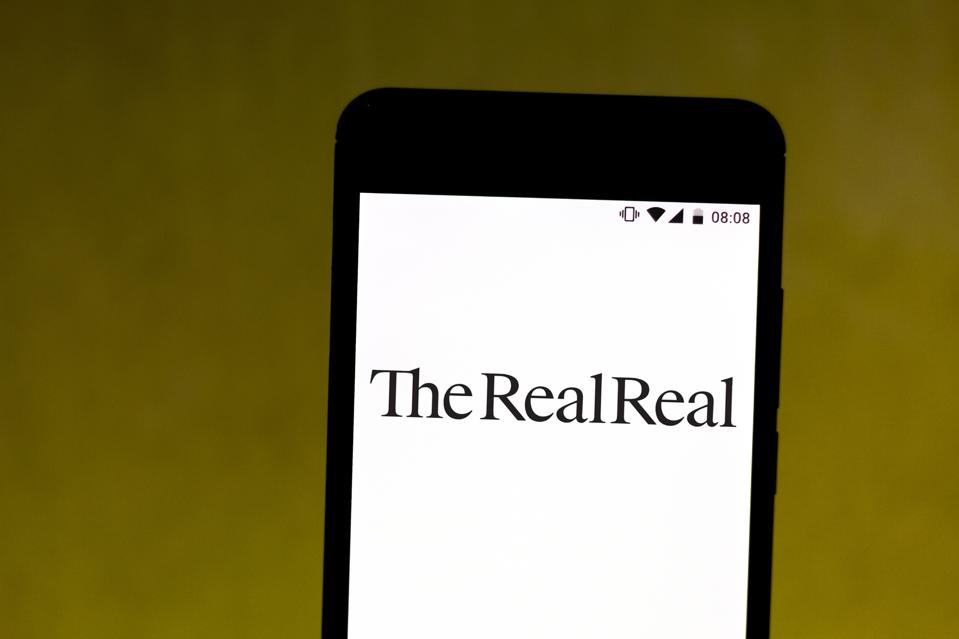 In this photo illustration The RealReal logo seen displayed...