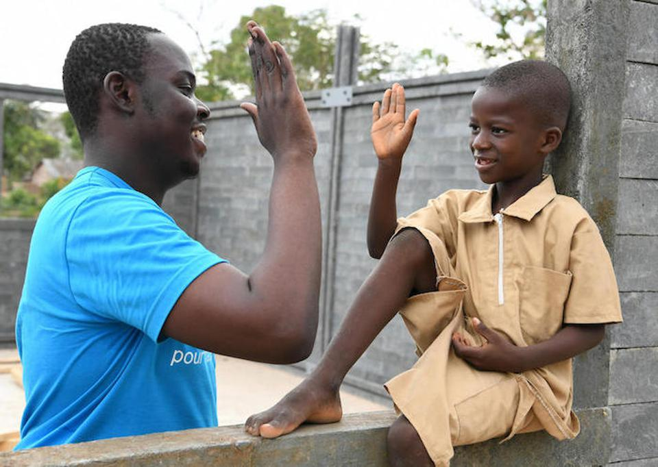 UNICEF staffer Stéphane Gbonikan and a young student celebrate a new classroom made of recycled plastic bricks in Sakassou, a village in central Côte d'Ivoire.