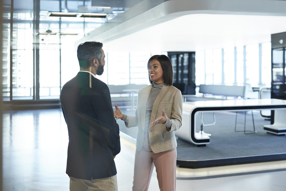 Stylish co-workers having discussion in office building