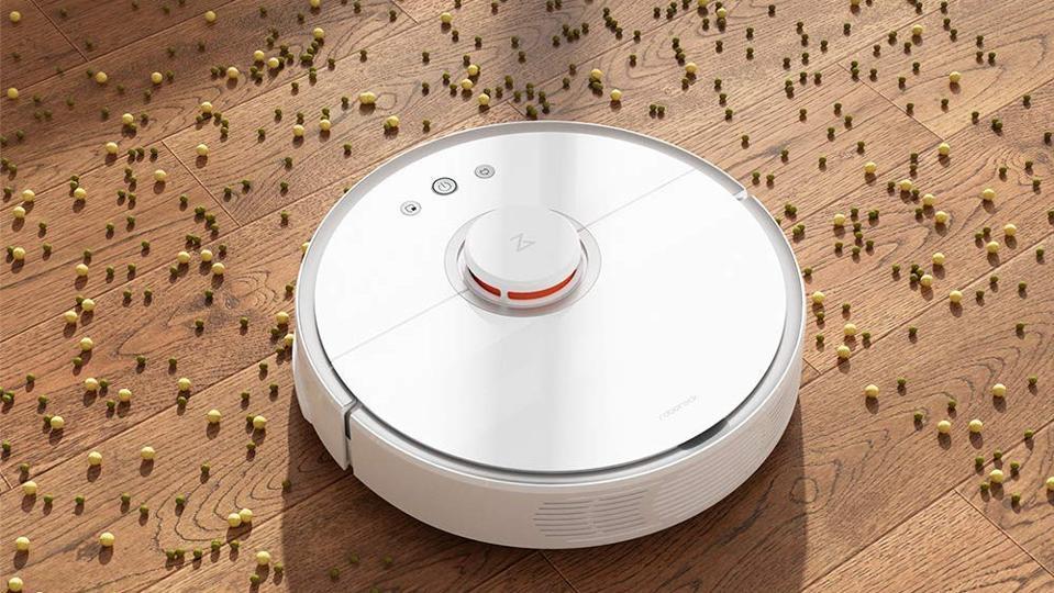 White robotic vacuum cleaning food on hard wood floors.