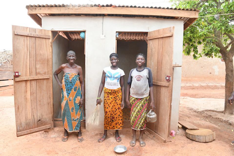 Dve mladi deklici pozirata z babico pred straniščem v vasi Dibobly, Slonokoščena obala. Prenaseljene četrti v mestnih območjih ustvarjajo sanitarne težave, s katerimi se inovatorji ukvarjajo s pomočjo UNICEF-a.