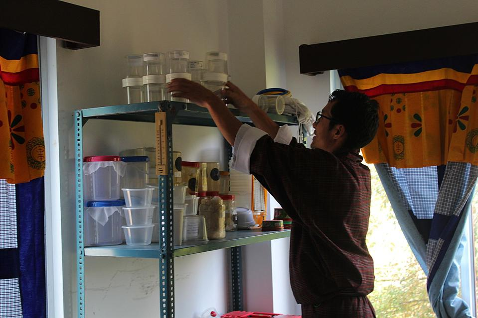 Man with glasses and dark hair reaching for sample jars