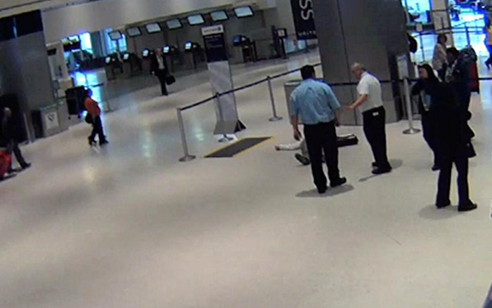 A screenshot of a male passengers shoved to the ground by airport agents in Houston.