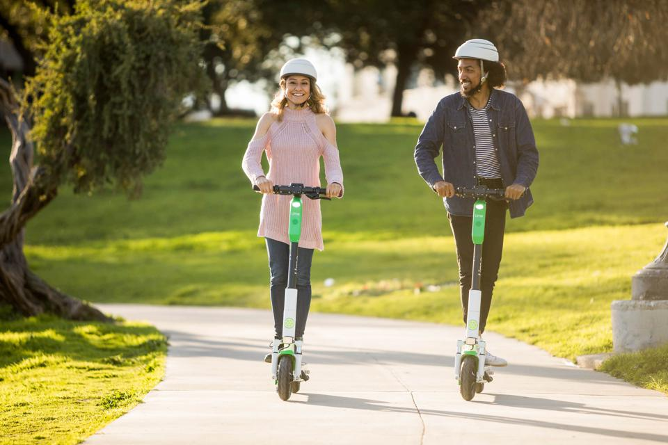Two Lime Scooter riders, smiling.