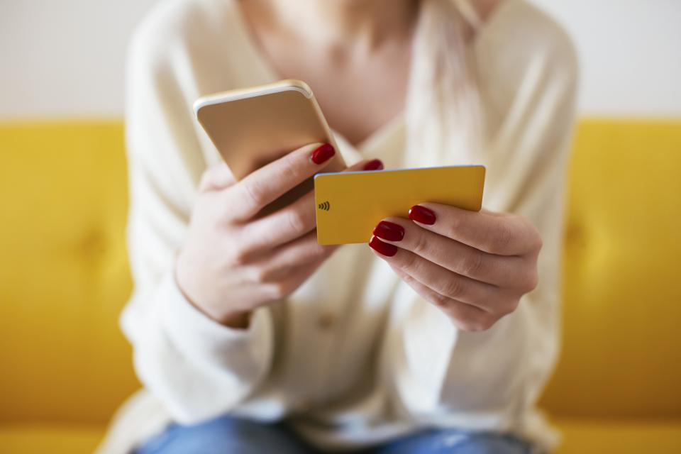 Blonde woman using smartphone and using bank card at home