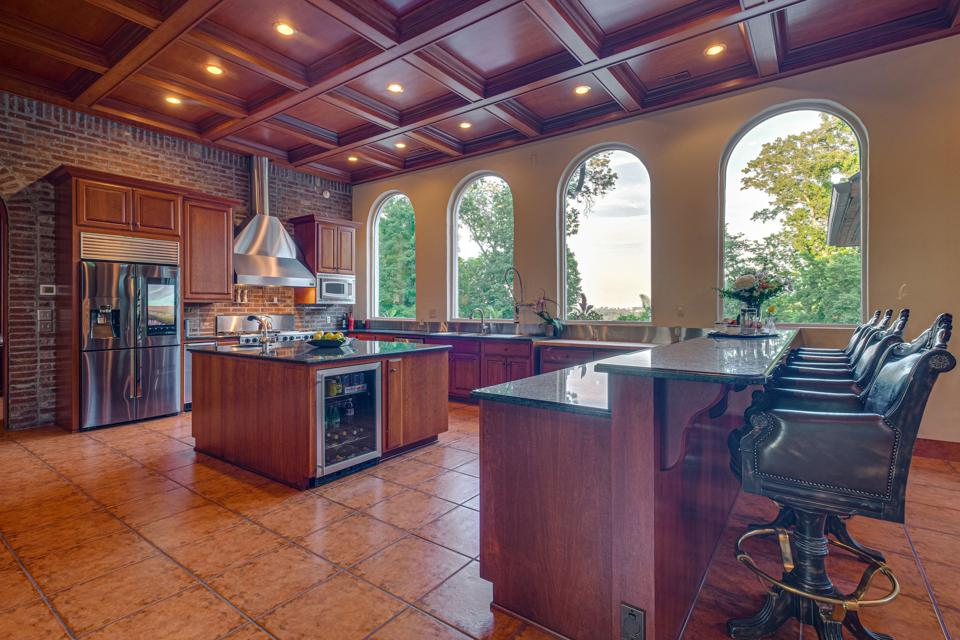The main kitchen features a solid cherry custom coffered ceiling, granite counters and an oversized island.