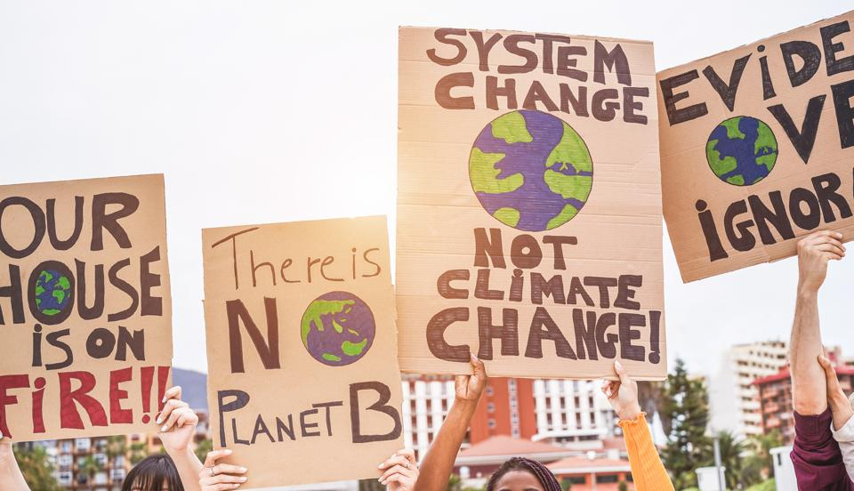 Group of demonstrators on road, young people from different culture and race fight for climate change - Global warming and enviroment concept - Focus on banners