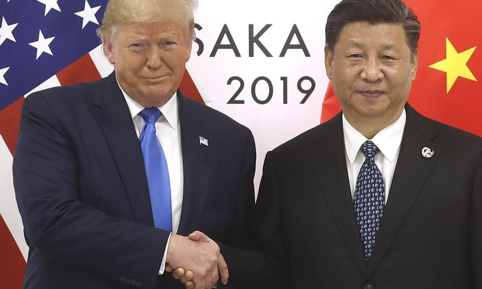 Chinese President Xi Jinping shakes hands with President Donald Trump in June in Japan. They are the primary actors in the longest-running, most serious trade war in history.