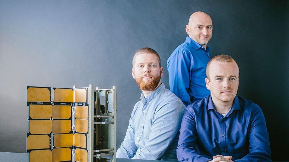 Spire's cofounders Jeroen Cappaert, Peter Platzer, and Joel Spark next to one of its satellites.