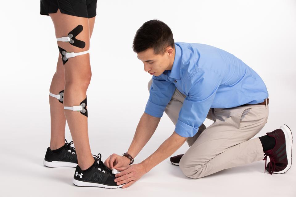 Technician straps Figur8 sensors onto a client.