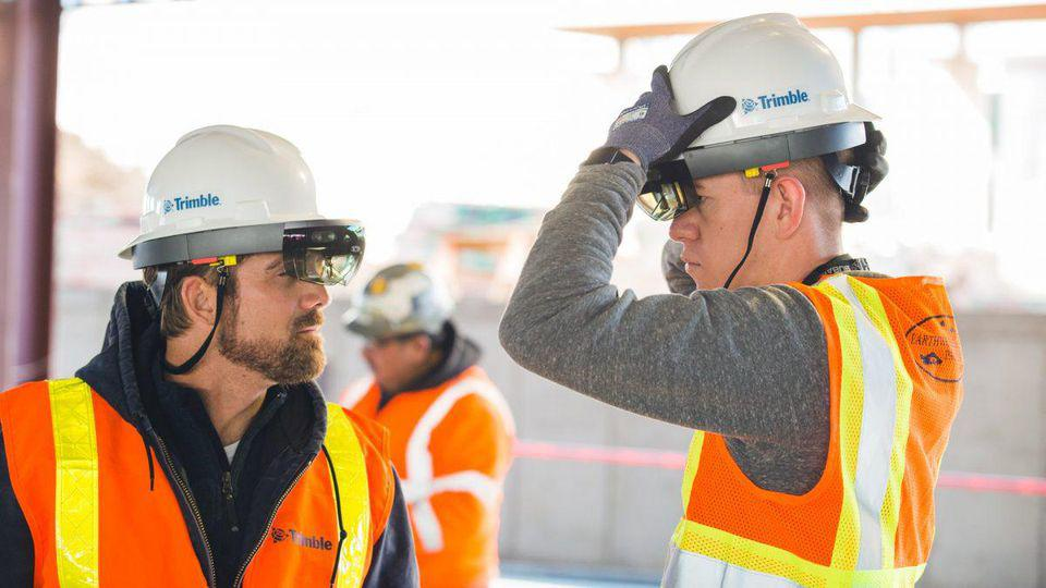 Men in hard hats with a mixed reality headset attached