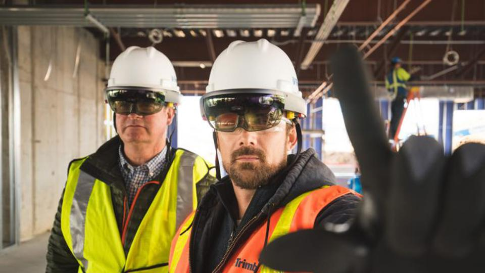 Two men in hard hats with mixed reality headsets attached
