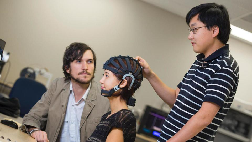 Three people, one woman wearing an EEG cap