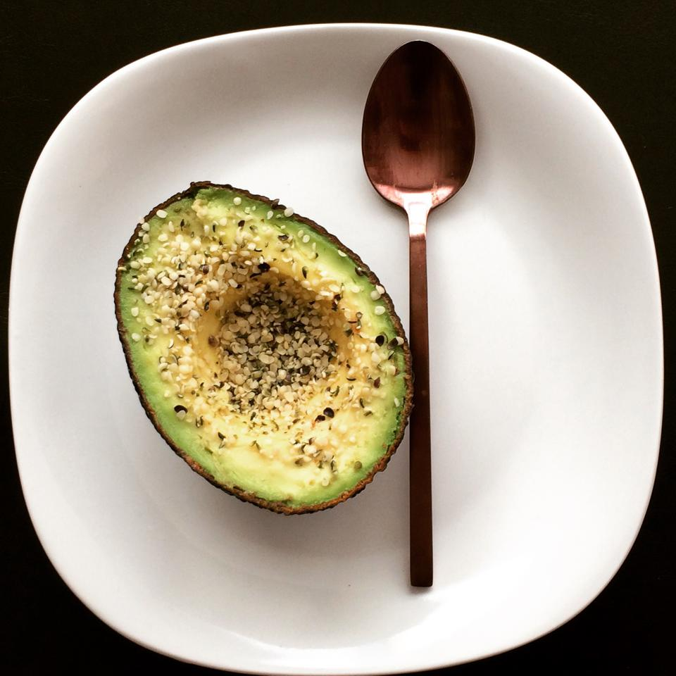 avocado with hemp hearts on a plate