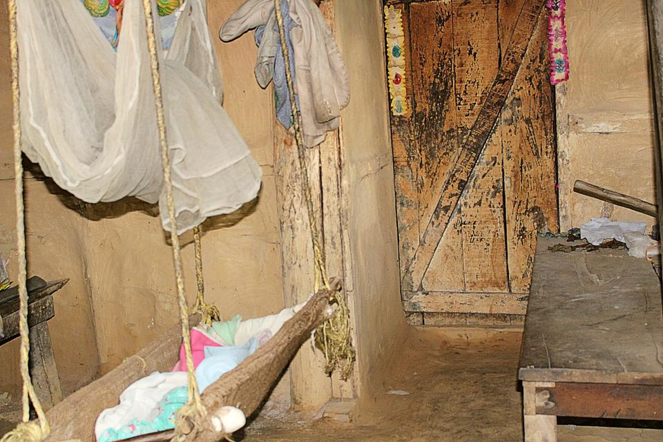 Hanging crib in a brown-walled house with a white mosquito net