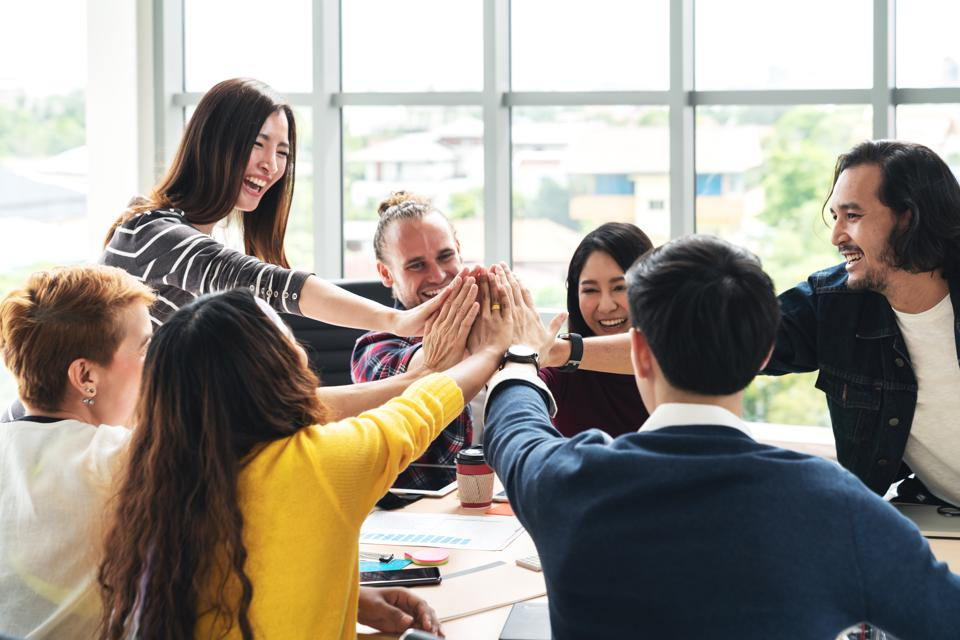 group of young multiethnic diverse people gesture hand high five, laughing and smiling together in brainstorm meeting at office.