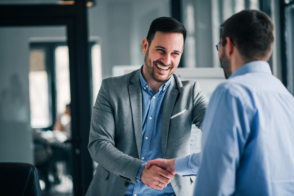 Business leader smiling while handshaking with new employee.