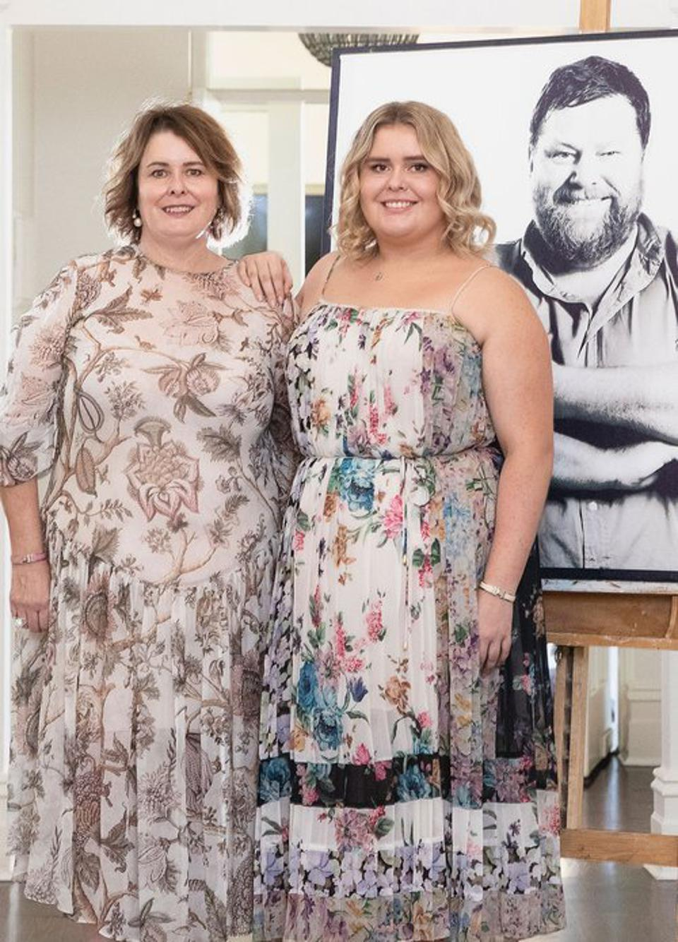 Kim and Margo Longbottom Standing Next to a Photo of Mark
