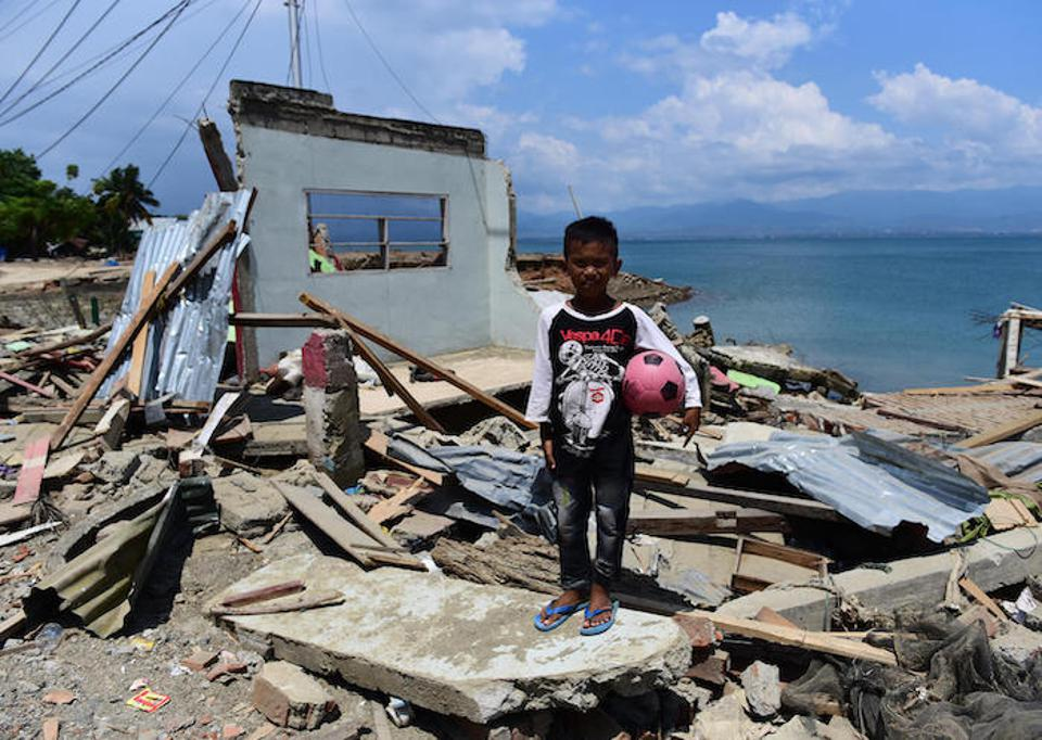 In Donggala, Central Sulawesi, Indonesia on October 3, 2018, 10-year-old Rido stands in front of his home, ruined by a tsunami in September 2018.