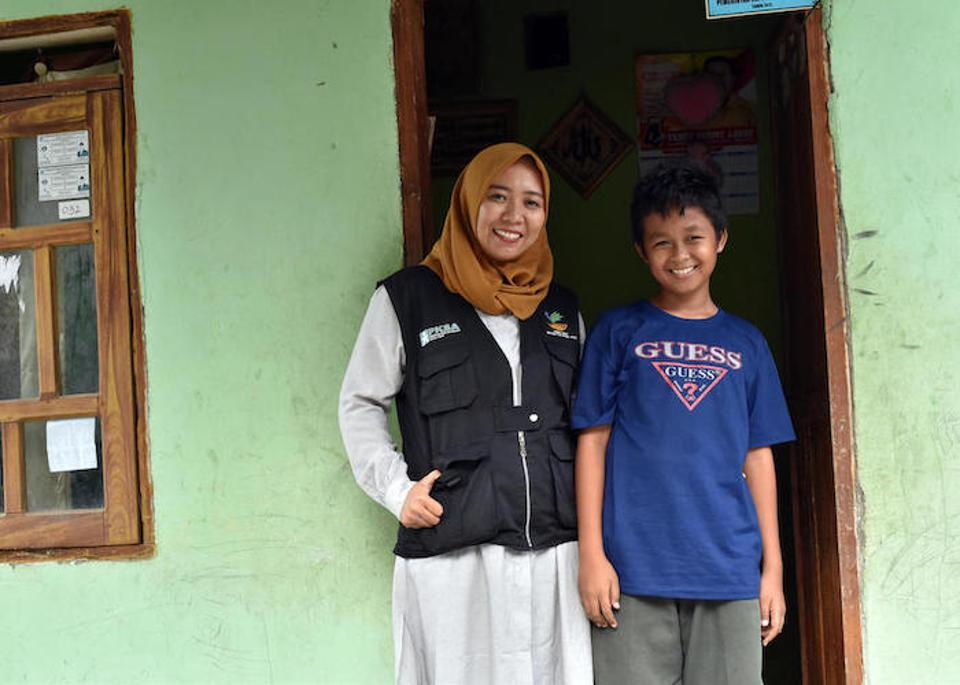UNICEF-supported social worker Chi Ramadhani checks in with Rivaldi, 13, outside his family home in Palu. Rivaldi was separated from his family for three days, until Ramadhani reunited him with his father.