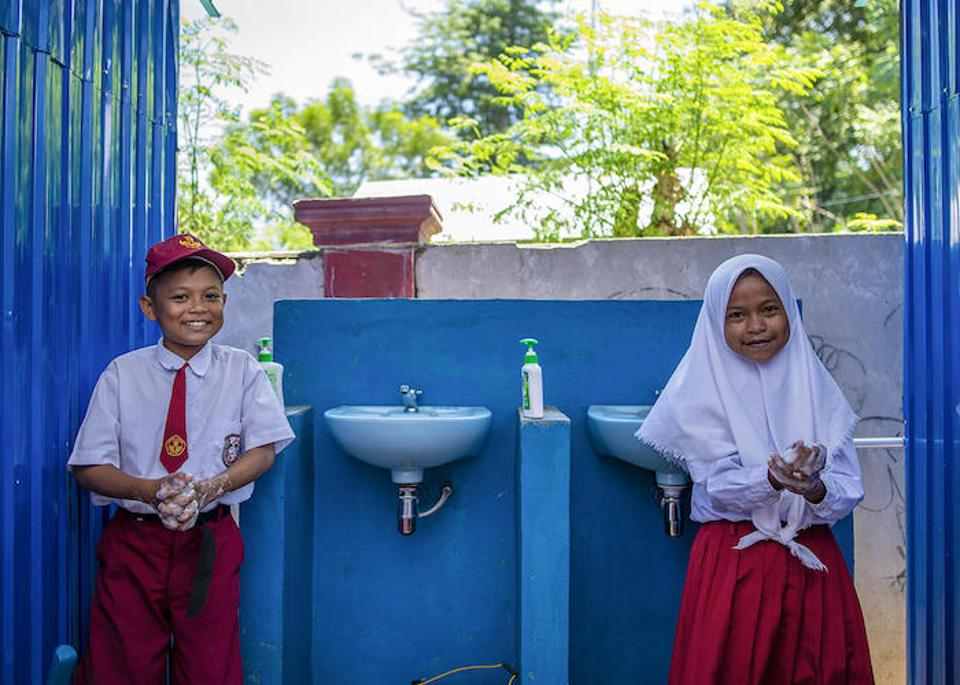 On September 9, 2019, 12-year-olds Biyan (left) and Sisal wash their hands at sinks installed by UNICEF at their school in Donggala, Central Sulawesi, Indonesia.