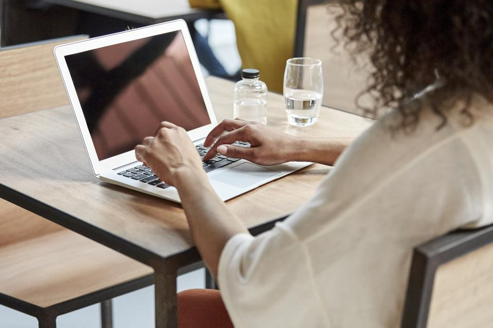 Businesswoman using laptop at table in cafe