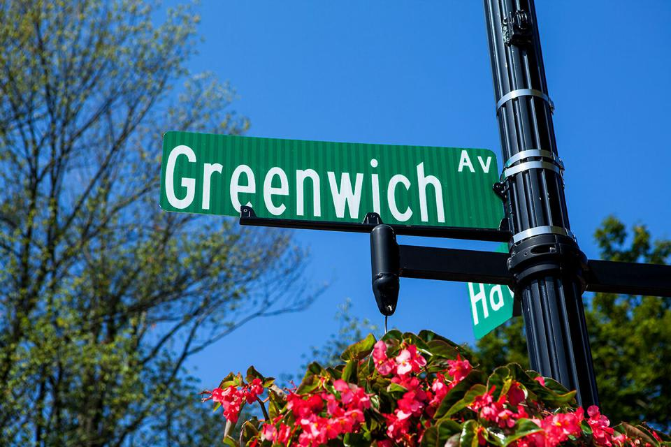 Greenwich Ave. street sign atop colorful flowers.