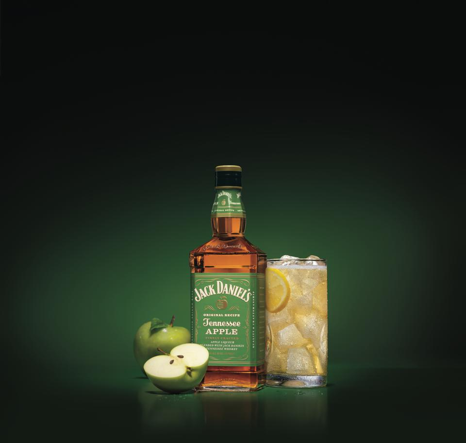 Bottle of Jack Daniel's Tennessee Apple surrounded by a glass and green apples.
