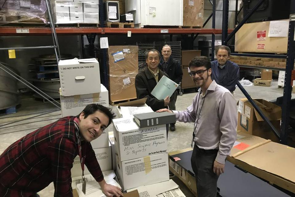 Color photo of a group of male engineers and scientists standing in a warehouse with a stack of boxes.