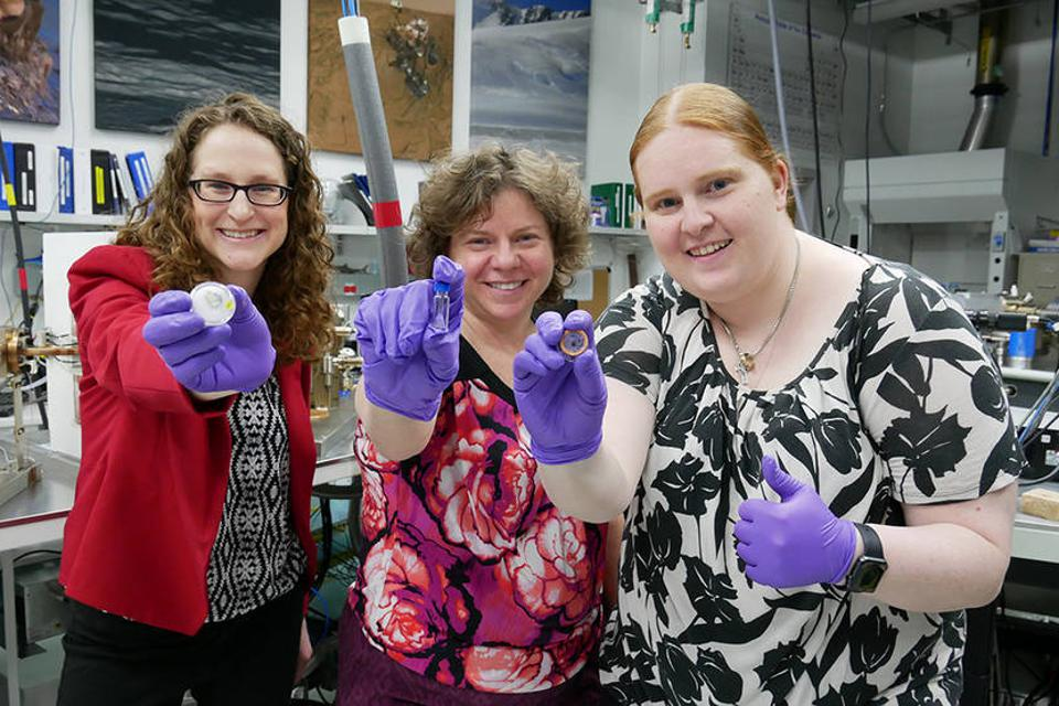 Photo of three female scientists in a lab, holding small containers of lunar samples and wearing purple gloves.