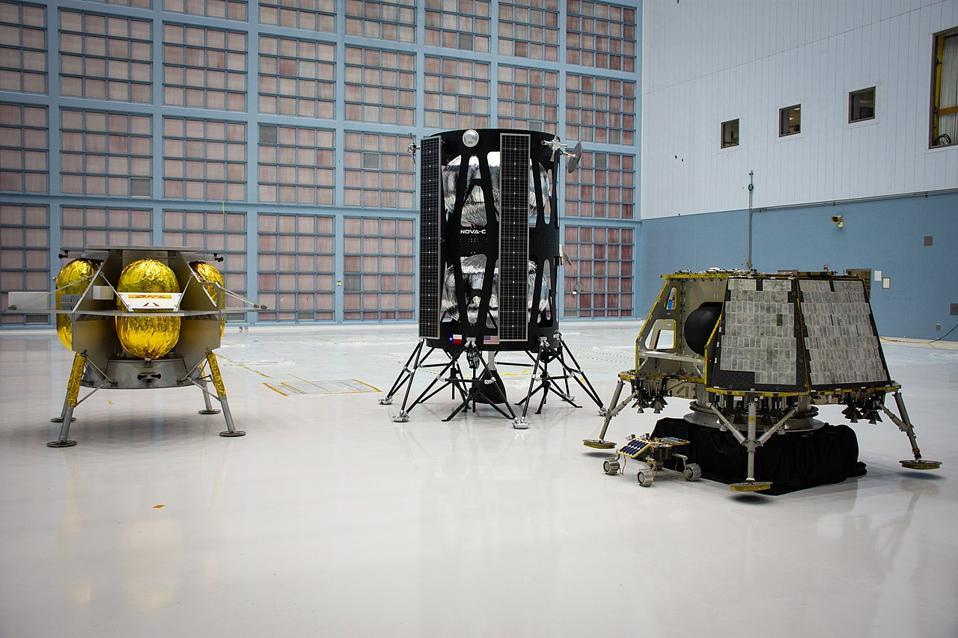 Photo of three lunar lander models in a hangar.