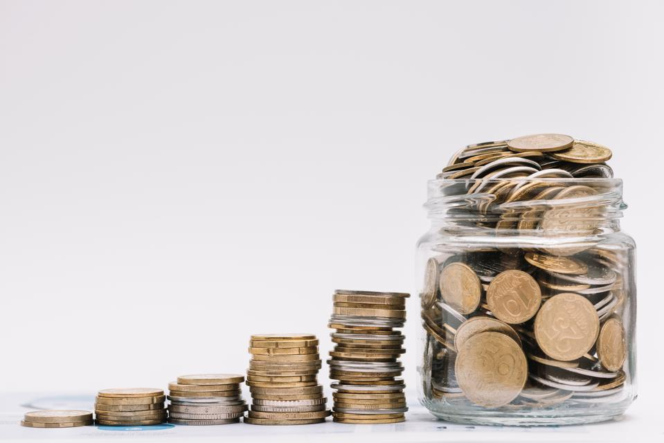increasing stacks of coins leading up to overflowing coin jar