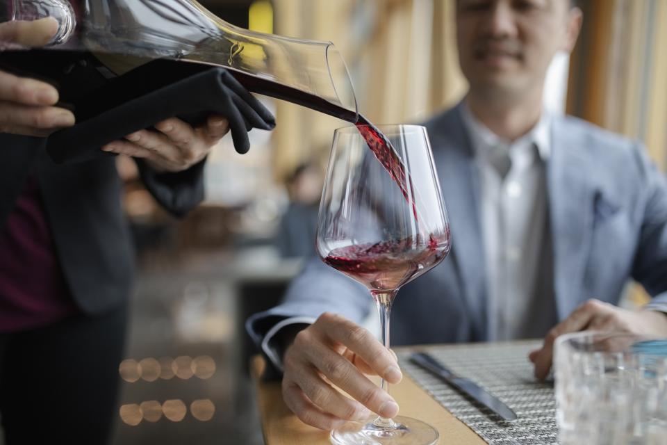 Sommelier versant du vin rouge pour homme dînant au restaurant