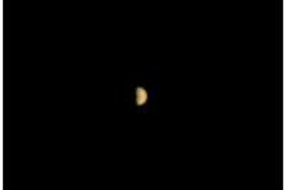 Color photo of distant Mars against the blackness of space.
