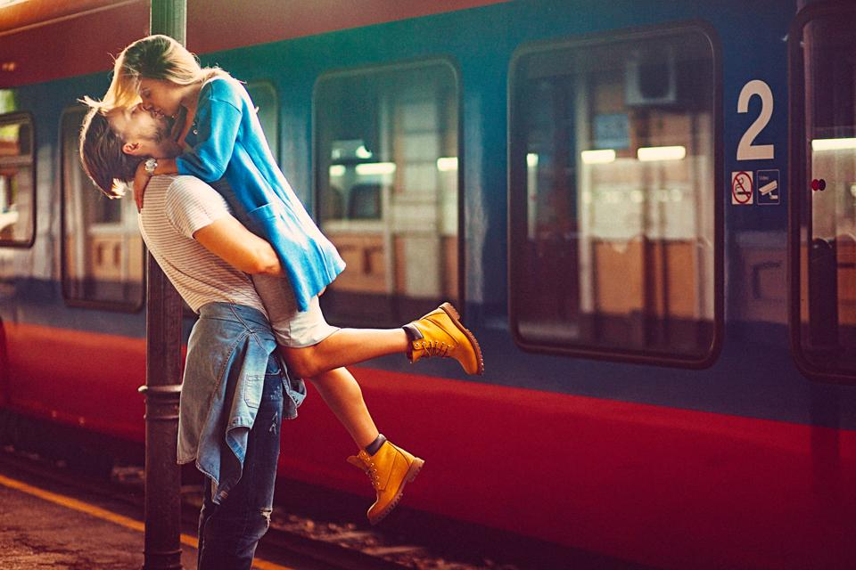 Passionate young man and woman kissing beside the train at the railway station