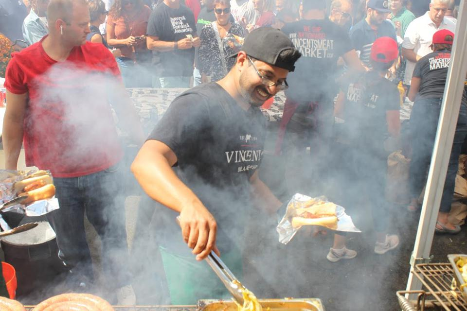 In a cloud of smoke, a cook serves up hot dogs in the unique NY style.