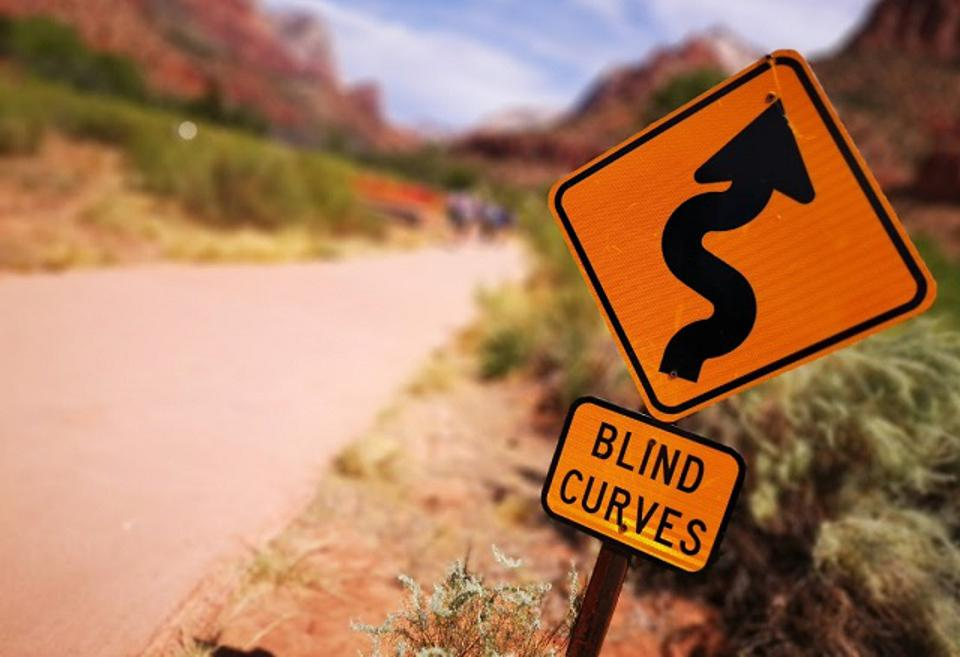 An image of a trail sign in Zion National Park that reads BLIND CURVES intended to show that the road ahead in technology is a twisty windy one.
