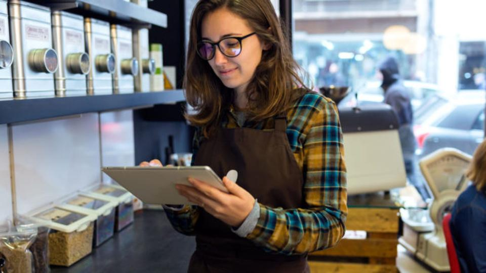 Female barista holding a tablet, smiling