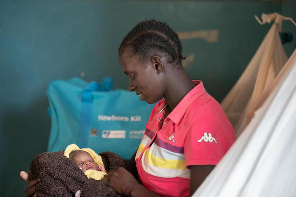 Above, Longom Esther holds her new baby, born at Kaabong Hospital in Uganda. Her newborn kit, provided by UNICEF and partner Korean International Cooperation AGency (KOICA) is packed and ready to go home with her.