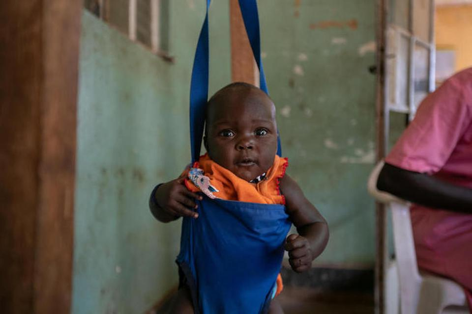 A baby is weighed before immunization at a UNICEF-supported health center in Uganda's Kaabong District.