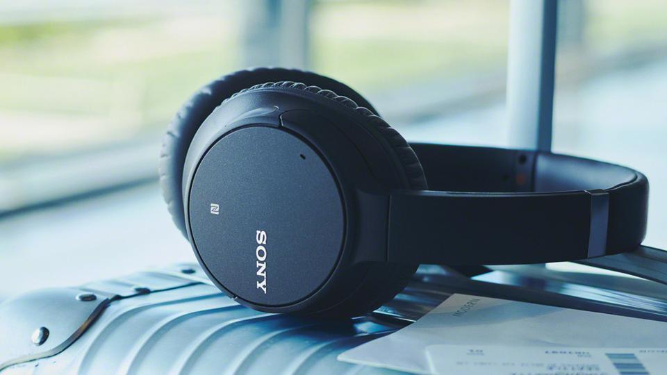 Black Sony WH-C700N headphones on a suitcase.