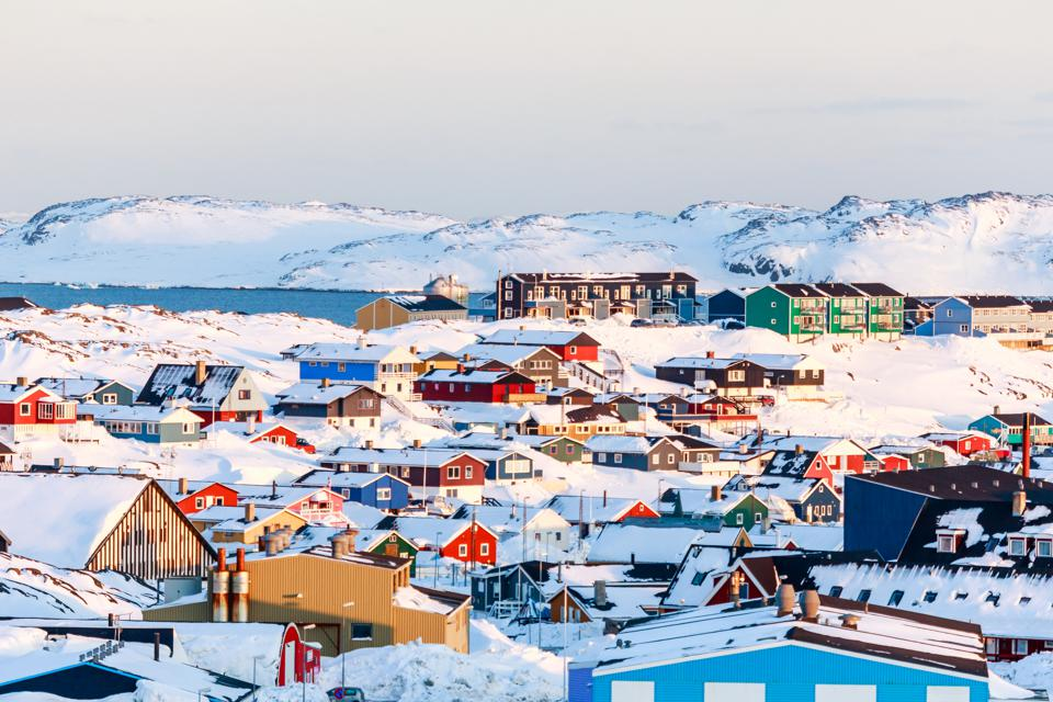 Lots of Inuit houses scattered on the hill in Nuuk city covered in snow with sea and mountains in the background, Greenland