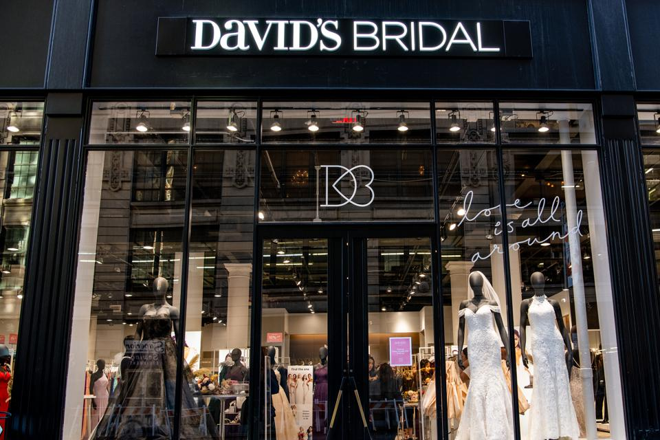 The David's Bridal store on 25th Street in Manhattan, with wedding dresses on display and a sign reading ″love is all around.″