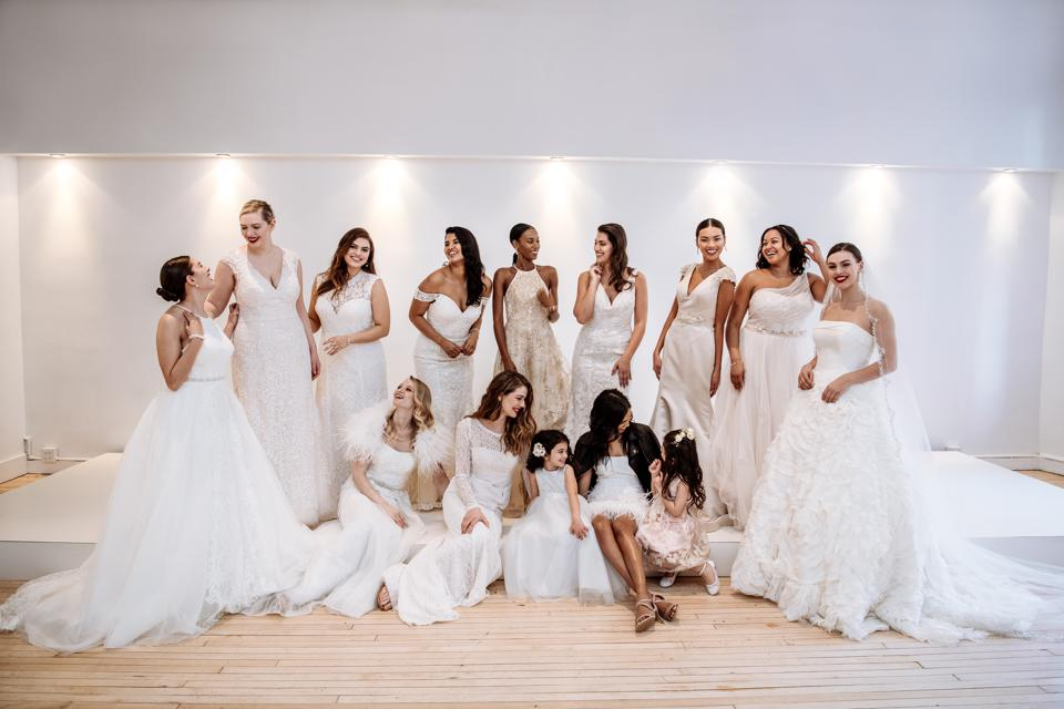 A photo of a dozen brides in wedding dresses and two flower girls.